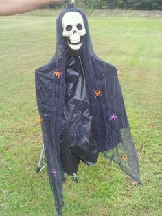 dollar tree skull, creepy cloth, black trash bag and plastic spider ring, hot glue and a wire hanger