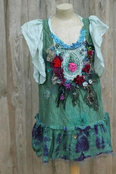 Light silk/viscose blend tunic, hand dyed in uneven shades of green; has been reworked with shabby chic torn and cut old lace details and embroidery/beading. The focal point is embellished applique at front of bodice with rich seed beaded details/pattern, accentuated with handmade