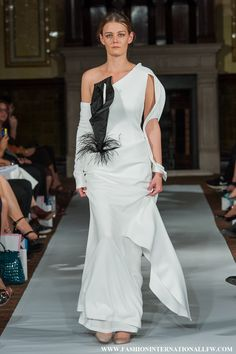 Lenie Boya, Spring/Summer 2015 London Fashion Week. Surrealist white dress, with 3D black calla lily detail and Futuristic bracelet sleeve.