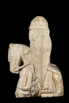 Chess-piece; walrus ivory; knight on horseback; damaged and split; hemispherical helmet and kite shield decorated with pelleted band forming cross over central circle; spear held in right hand.Side view after cleaning