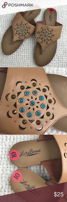 NWOB Lucky Brand tan perforated jeweled sandals Super cute shoes perfect for next summer. Never used. Faux leather upper in a neutral tan camel color. Beautiful design made of perforated moins and triangles as well as little turquoises and bronze pointy studs. Size 10B/M length 10 3/4in width 3 1/2in. Lucky Brand Shoes Sandals