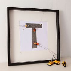 Personalised Construction Toy Letter Art by Berties - GBP 53.75 »  Monograms are a great way to personalize a kid's space. This 3D construction version is made of a gravel-textured surface with toy diggers, dumper trucks and even workmen. My favorite parts are the muddy tracks leading off the print and onto the mat board — almost like the machines have been busy working while your child slumbered.