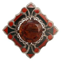 Fine Victorian Scottish Agate Brooch Scotland  1860-1880  A mini mosaic of agate with silver accents designed like a piece of art.  Notice the seamless joining of the agates while keeping in mind that all this work, the silver settings and engraving, the beautiful silver details and the stone cutting and polishing were done by hand 150 years ago. At center is a faceted citrine.  A strong appearing brooch with beautiful design. All original and a fine example of Scottish jewelry.