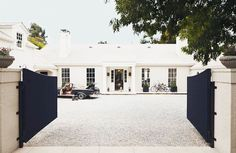 Black curved gates open to beautiful home with columns framing front entrance.