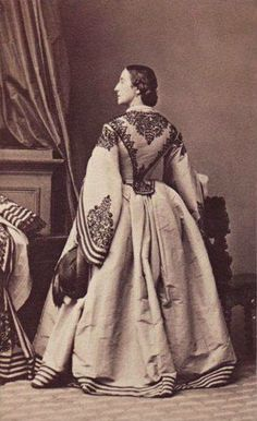 1860s Civil War Era picture of a woman in a light dress with beautiful trimming.