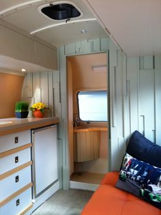 small kitchen in trailer with wooden cabinet, brown counter top, turquoise wall, white ceiling, orange couch, blue pillow of Trailer with Everything You Need Inside