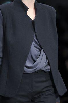 GOSTO do paletó sem botões, do colarinho curto e contemporâneo, ombros delicados... GOSTO da calça com cós fechado, cintura levemente baixa, corte parece confortável.