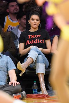 Kendall Jenner sits courtside in a Dior Addict t-shirt, cuffed jeans, hoop earrings and Yeezy boots. See more of the model's best outfits here: