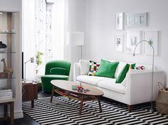 Olohuone, jossa valkoinen sohva, pyörivä lepotuoli ja pähkinäpuinen sohvapöytä.