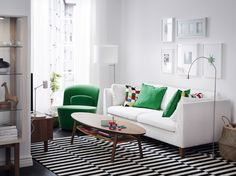 A light living room furnished with a white three-seat sofa and an easy chair that swivels, covered with green velvet. Shown together with an oval coffee table in walnut.