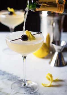 //French 75//  INGREDIENTS (MAKES 1 COCKTAIL): 2 ounces gin (I used Hendrix), 1 ounce freshly squeezed lemon juice, 2 teaspoons of sugar, Dry champagne or sparkling wine (I used my favorite brut; Veuve Clicquot), Garnish with lemon spiral and a cocktail cherry (I used Luxardo Cherries)