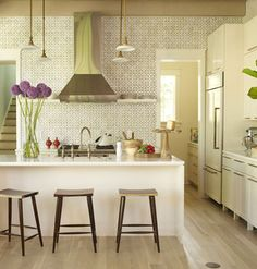 An entire wall covered in handmade Italian tile (Nottingham Honeycomb ceramic tile in Veil by Ann Sacks), transforms the kitchen's back wall into a textured mosaic. Open shelving allows the fabulous tile to be the center of attention in this clean kitchen