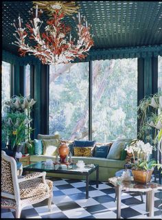"DESIGNER HUTTON WILKINSON DECORATED THE GARDEN ROOM AT DAWNRIDGE, TONY DUQUETTES HISTORIC HOUSE IN BEVERLY HILLS WITH A BLACK AND WHITE FLOOR, AND TONY DUQUETTE FOR JIM THOMPSON ""GEMSTONE"" FABRICS IN LAPIS LAZULI AND MALACHITE.  THE GIANT CLAM SHELL ETAGERES WERE DESIGNED BY DUQUETTE TO DISPLAY PLANTS.  WILKINSON CREATED THE CORAL BRANCH IRON AND LUCITE CHANDELIER, USING ELEMENTS FROM THE DUQUETTE WAREHOUSE OF MATERIALS."