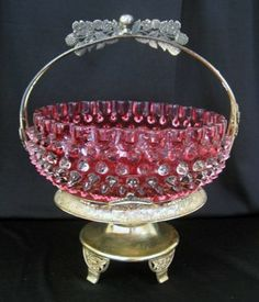 Cranberry glass hobnail bride's bowl in gold metal basket stand,