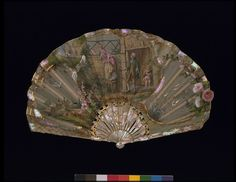 The main charm of this fan is the way the image on the front is seen from behind on the reverse.  A young woman talks to her lover over a fence while her father looks on.  On the reverse, the lover reaches up to talk to his sweetheart.  The rounded shape of the fan leaf and green tinting of the mother-of-pearl are typical of the period 1895 to 1905