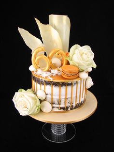 Chocolate mudcake with white buttercream in a semi naked finish. It is decorated with a salted caramel drip and topped with salted caramel macarons, meringue kisses, white chocolate shavings and white chocolate sails with gold dust. I've also added a gold fondant 60 and fresh white roses. www.facebook.com/cakesbyleannerhodes
