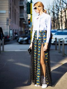 Street style star Veronika Heilbrunner wears a button-up top with a fishnet, printed pleated carwash skirt, white tennis shoes, sunglasses and simple jewelry.