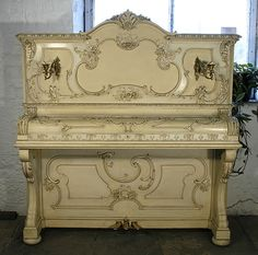 A 1903, Ibach upright piano with a rococo style case and gilt detail at Besbrode Pianos.  Case covered in asymmetrical, ornate carvings of flowers and scrolls.