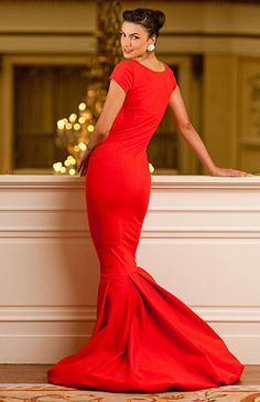 Karen Caldwell Design, Veronica  Dramatic evening gown, with scooped neck, fitted waist, with billowing fabric bottom. Lined in 100% silk. Shown in poppy red.