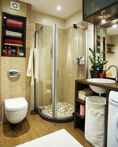 Efficient bathroom- small spaces. Wall hung toilet, smaller shower stall, over vanity cabinet, under sink hamper, and a washer under sink vanity.