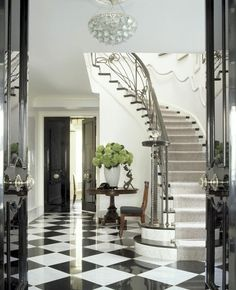 The sweep of the staircase up from the checkerboard floor, the black doors in fore- and background, the glass door knobs, even @ the staircase. Wowie wow. :)