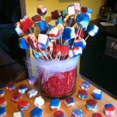 Star marshmallow dip in melted candy with sprinkles. Jar filled with hot tamales.