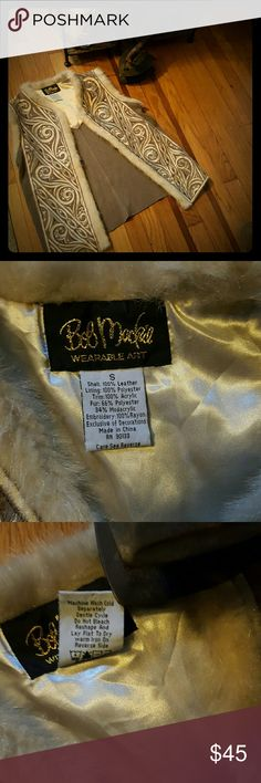 🍃🌺BOB MACKIE WEARABLE ART VEST🌺🍃 Beige, taupe, silver/gold threads designs in the front area. We know Bob Mackie as the designer of many stars, Carol Burnette  was his most known as was Barbara Streisand. This vest has faux fur on top area of arms and from neck to the bottom. The shell is 100%leather lining is 100% polyester trim is 100%acrylic. Fur 66% polyester 34%modacrylic.  Embroidery 100%rayon Exclusive of decoration. It has stretch due to the material used on back. It can also be…