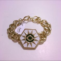 White & Gold Sun Eye Chain Bracelet This gold chain toggle bracelet features a white hexagon emblazoned with a 12-point sun that has an eye in the center. Starlet Fever Jewelry Bracelets