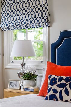 INTERIORS BY HIGHGATE HOUSE   Graphic embroderied navy and white roman blind with custom made blue and white bedhead with a touch of tangerine