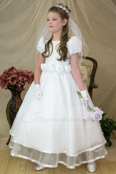 First Holy Communion Dress with Short puf sleeves and bateau neckline highlight satin bodice. Five satin roses adorn the waistline. New tulle skirt trimmed with satin at hemline.