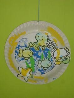 Hanger met onderwater dieren. Twee kartonnen bordjes laten verven en uit een een ronde cirkel knippen. Bordjes op elkaar lijmen. Kleurplaat met waterdieren laten inkleuren/verven. Uitknippen en in de hanger laten plakken. Strookjes groen papier scheuren en erbij plakken. Aan de bovenzijde van de hanger een gaatje maken. Touwtje erdoor en klaar is de hanger!