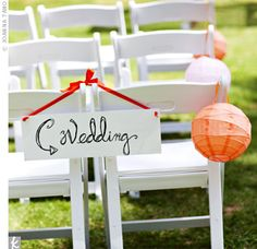 "Alyson lined the aisle with coral, tangerine, mango, yellow, and chartreuse paper lanterns. She and her father also hand-painted signs that read ""wedding,"" ""croquet,"" ""feast,"" and ""merriment"" and hung them around the wedding site."