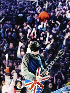 """Noel Gallagher with his Epiphone Sheraton Union Jack Guitar. """"Yeah, epiphones are cheap guitars.it's OASIS for gods sake! These guitars rock! Noel Gallagher, Liam Gallagher Live, Oasis Band, Pop Rock, Rock And Roll, Great Bands, Cool Bands, Banda Oasis, Rock Festival"""