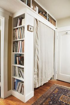 Turn a bookshelf outward, add a hanging rod and a curtain for a home-made closet.