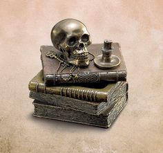 Skull and Books Trinket Box   In the alchemist's study, a skull sits atop a stack of volumes. What arcane knowledge do they hold? Lift the top volume to reveal a hidden space for your secret treasure