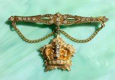 This large vintage 1970s clear rhinestone gold-tone figural dangle crown pin / brooch is ornate, with a decidedly Victorian Revival flair. Also known as a collar or bar pin, its lightweight, well-made, and in wonderful vintage condition. It would make the perfect gift for your favorite crown (or tiara!) enthusiast. New items are added daily so I hope youll come back to visit Figurally Speaking again soon: http://www.figurallyspeaking.etsy.com Thank you for stopping by. :-)