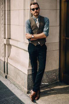 Acheter la tenue sur Lookastic:  https://lookastic.fr/mode-homme/tenues/gilet-chemise-en-jean-pantalon-de-costume/14531  — Lunettes de soleil noir  — Chemise en jean bleu  — Cravate imprimé beige  — Gilet en laine brun foncé  — Montre en cuir brun foncé  — Pantalon de costume bleu marine  — Double monks en cuir bruns