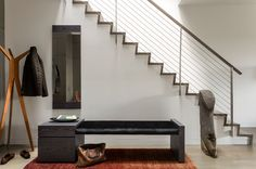 """""""The entire house is unified with oak flooring with a custom warm gray stain. This material is repeated on the stair and atrium handrails,"""" Walker said. The entryway's bench has a custom Tabu Caleidolegno veneered wood base. The upholstered bench seat, which uses black Kravet fabric, was designed by Ruhl Walker Architects and made by Herrick & White."""