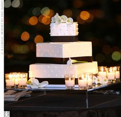 Iced in champagne-colored buttercream and decorated with Swiss dots, each tier of the square cake was placed at an angle and accented with a chocolate brown-colored ribbon.