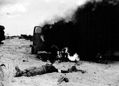 JUN 6 1944.  1500: Omaha – the battle continues Some of the casualties on Omaha beach, vehicles still burning , although it is quite late in the day after barrage gallons went up.