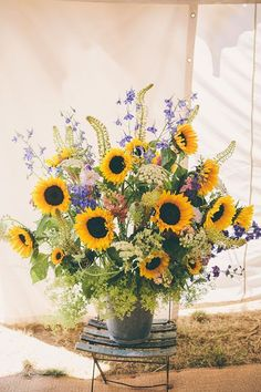 Leona and Ed Wedding flowers. The centrepiece of the marquee was a big bucket of sunflowers and wildflowers, which sat on a rustic chair.