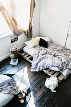 Beautiful contrast with the dark timber floors and raw pallet bed. Love the pulled draped curtain