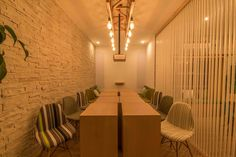 Modular workstations that come together to form a collaborative chef's table style working space. Wooden lamp crafted with edison bulbs illuminate this space. Custom Eames chairs add more colour to the coworking space