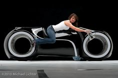 "Street-Legal Tron Light Cycle: Designed for ""casual cruising"" and slow ride-bys with a steel frame and a fiberglass cowling with electroluminescent strips. Powered by a fuel injected Suzuki 886cc, 4 stroke engine. $55,000"