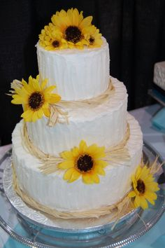 Sunflower wedding cake with textured buttercream and raffia.