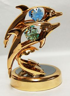 Playful Dolphins Figurine - Swarovski Crystal Elements  --  These playful dolphins are a wonderful representation of being free in the sea! They're quite attractive in their 24k gold plated finish and to top it off, their Swarovski crystal elements are blue and green, reminiscent of the blue-green sea where they play and live. In your home or office, this lovely piece will shine and glimmer when it connects with light.
