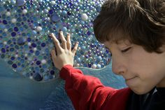 Cole Massie, 12, feels the texture on the sensory wall at the universal access playground at Anthony C. Beilenson Park at Lake Balboa. The sensory wall was built by Lexington Design + Fabrication, of Pacoima, and Shane's Inspiration, a Van Nuys whose mission is to create universally accessible playgrounds and programs that socially integrate children of all abilities. (Michael Owen Baker/Staff Photographer) #InclusivePlay