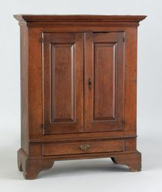 Rare Chester County, Pennsylvania, walnut linen cupboard, circa 1780, the molded cornice over two raised panel doors, above a single drawer supported by bold bracket feet, 49.75 H. x 34.75 W.