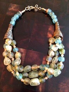 Two antique hair beads from Cameroon with a gorgeous patina are used as cones to envelop three strands of mixed phrenite stones and recycled bottle glass beads from Ghana.