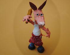 Burro cocinero: modelado en papel maché sobre estructura de almbre, cabeza de telgopor, orejas y dientes de cartulina, palo de amasar y pies de masilla epoxi.